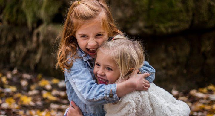 Zwei sich in die Arme nehmende Mädchen.