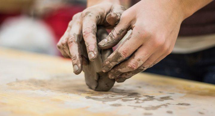 Kinderhände, die mit Ton arbeiten.