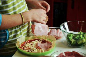 Kinderhände beim Pizzabacken