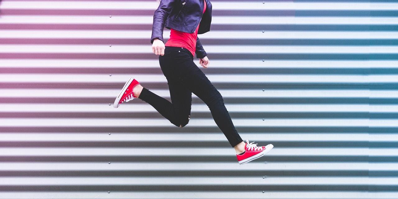 Springende, junge Frau mit roten Converse Schuhen