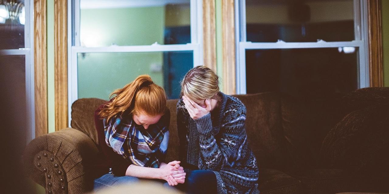 Zwei Frauen, die auf einem Sofa sitzend zusammen beten.
